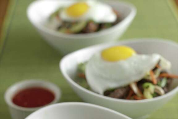 Bibimbap is a Korean dish of mixed vegetables and meat over rice with hot sauce.