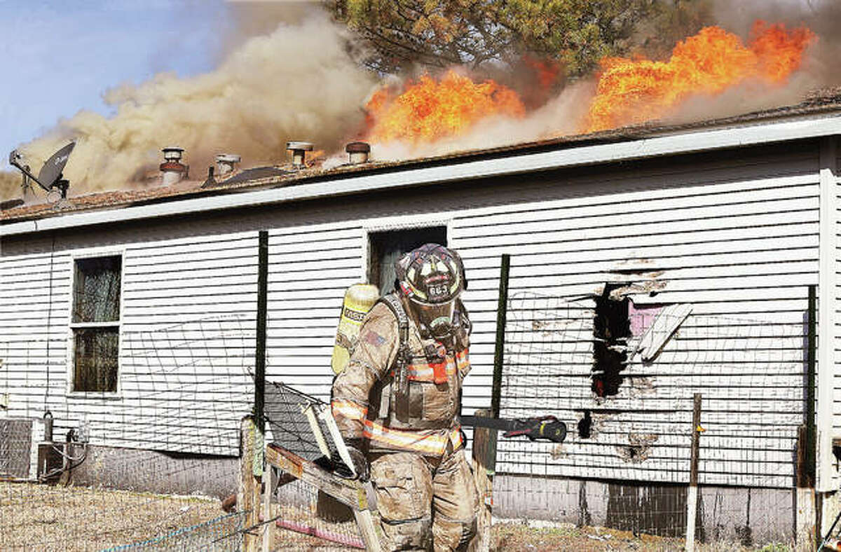 A firefighter drags a hose line to a new location Tuesday as flames break through the roof of a house in the 3500 block of New Poag Road, about 300 yards east of Illinois Route 3 in Hartford. The house, which was gutted by the wind-swept fire, was in the Mitchell Fire Protection District but had a Hartford mailing address. Firefighters from South Roxana, State Park, Troy, Holiday Shores and the Long Lake fire protection districts were called to the scene for assistance. Water had to be brought to the fire by tanker truck. Police from Hartford and South Roxana closed New Poag Road in both directions to allow firefighters to work.