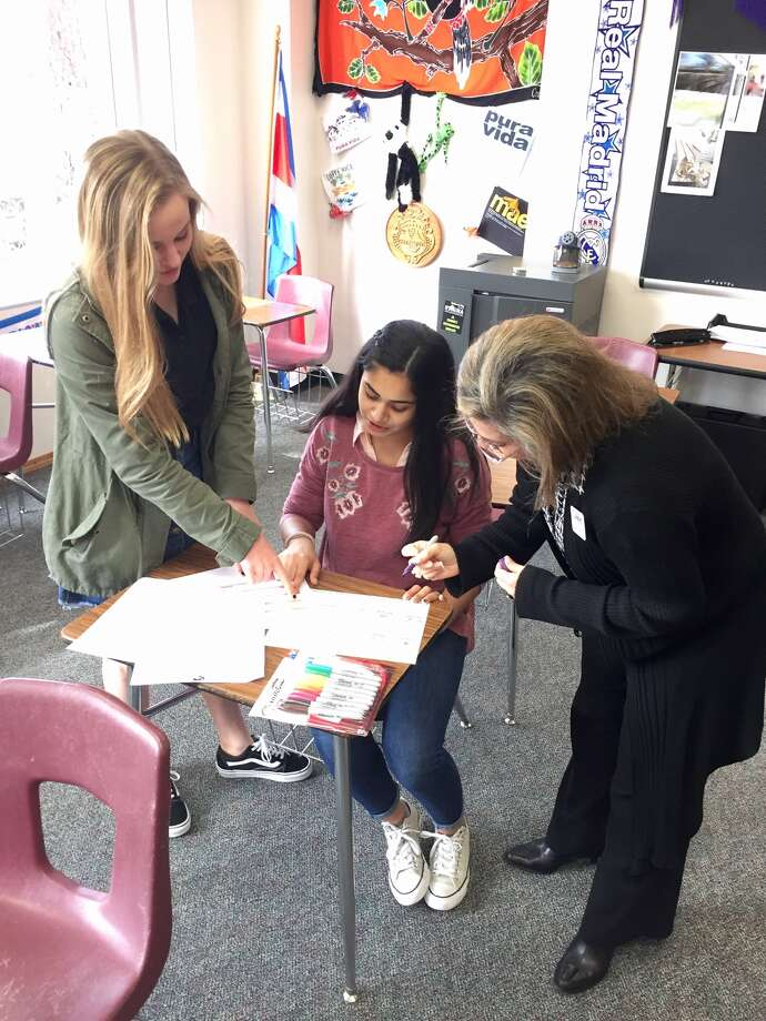 "Sophomore Avery Schlichter (left), advisor Marivi Mata, and sophomore Alena Fayaz devise a plan for ""Stamping Out Exclusion"" at The John Cooper School. Photo: Julie Cornell/Special To The Villager"