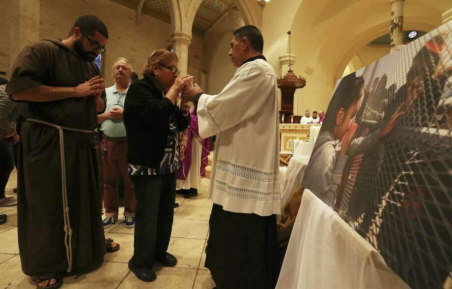 Acolyte Juan Espinoza (center) helps with communion beside an altar highlighting the plight of immigrants as a Catholic Mass was held at San Fernando Cathedral presided by Archbishop Gustavo Garcia-Siller on Tuesday, Feb. 27, 2018. The service was attended by Tex-Mex Border Bishops and was open to the public to pray for and celebrate immigrants and DACA recipients. The mass was held in conjunction with a conference of Catholic bishops from the border and which is focused on immigration issues.  (Kin Man Hui/San Antonio Express-News) Photo: Kin Man Hui, Staff / San Antonio Express-News / ©2018 San Antonio Express-News