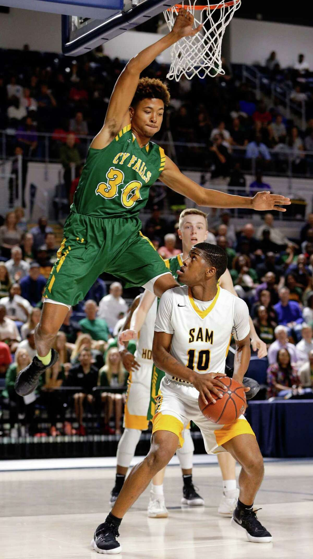 Sam Houston's Chris Green (10) waits to put up his shot as Cy Falls' TJ Goodwin (30) flies by during the first half of their regional quarterfinal game at Delmar Fieldhouse Feb. 27, 2018 in Houston, TX. (Michael Wyke / For the Chronicle)