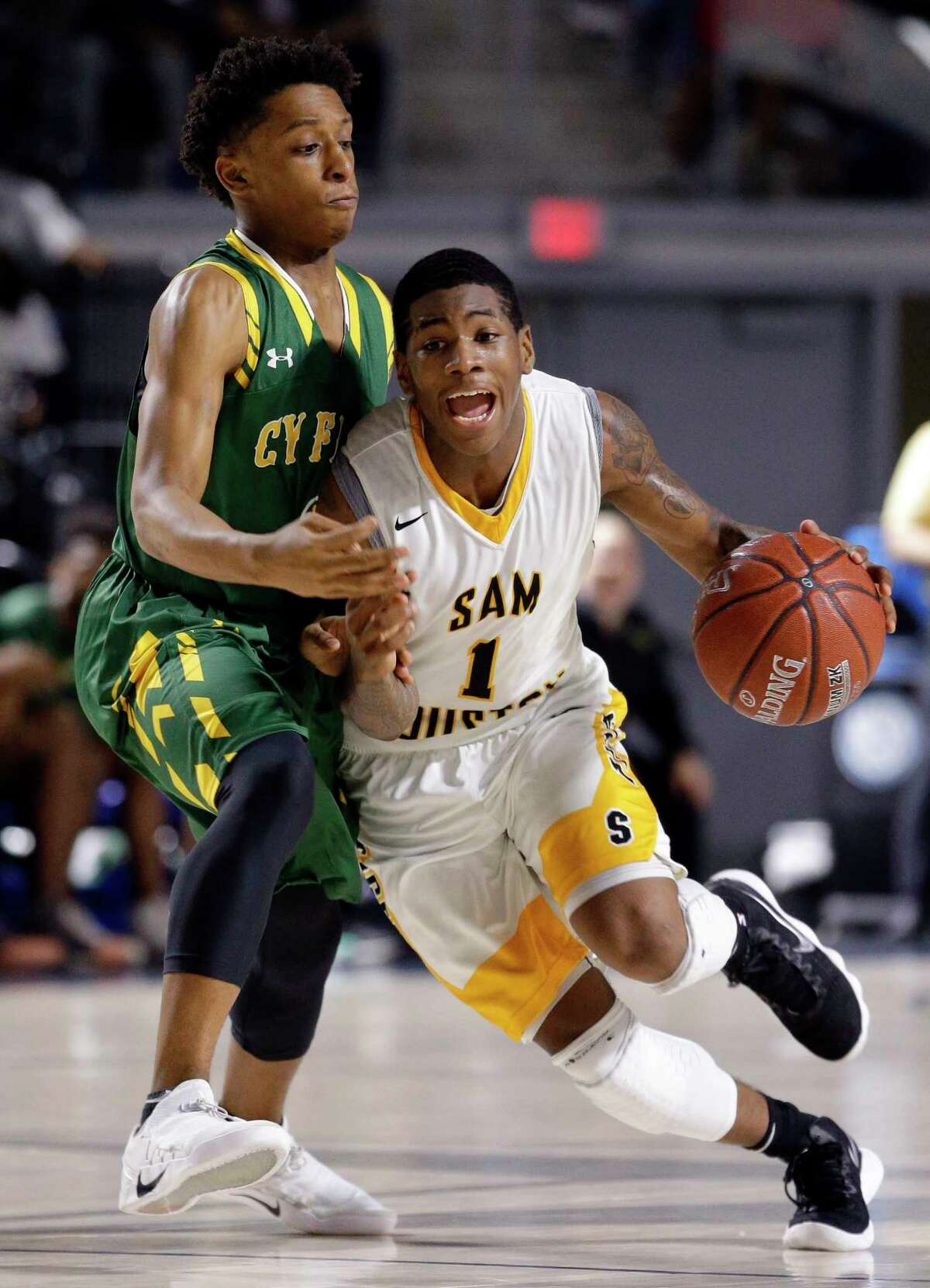 Sam Houston's Kendric Davis drives past Cy Falls' Austin Guillory during the 2nd half of their regional quarterfinal game at Delmar Fieldhouse Feb. 27, 2018 in Houston, TX. (Michael Wyke / For the Chronicle)