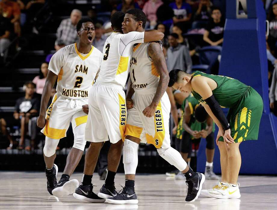 Sam Houston's Torron Mingo (3) hugs Kendrick Davis (1) as Marlon Jackson yells and Cy Falls' Andrew Nguyen reacts after Sam Houston wins in double overtime in their regional quarterfinal game at Delmar Fieldhouse Feb. 27, 2018 in Houston, TX. (Michael Wyke / For the  Chronicle) Photo: Michael Wyke, For The Chronicle / © 2018 Houston Chronicle