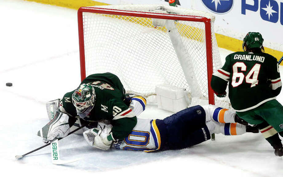 The Blues' Nikita Soshnikov crashes into the post and Minnesota Wild goalie Devan Dubnyk, left, after he was tripped by Mikael Granlund, right, Tuesday night in St. Paul, Minn. Photo: AP