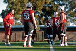 Offensive line coach Kevin Carberry, left, working with his players during practice for the Stanford football team at Stanford, Calif., on Tuesday, February 27, 2018.
