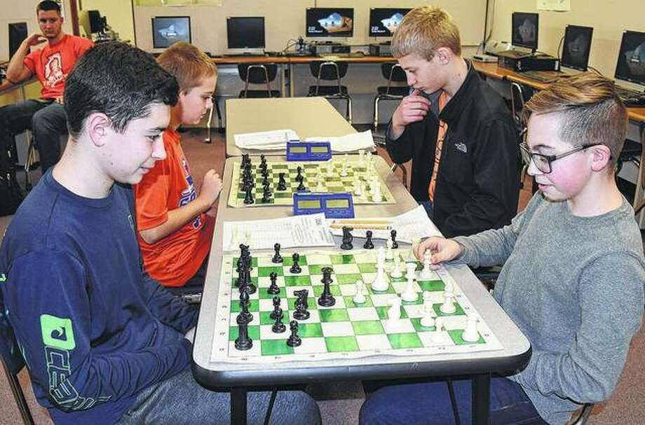 Seventh graders Tristan Turner (counter-clockwise), Cole Delaney, Thad Bergschnider and Isaac Carter play some practice chess games Tuesday. Photo: Samantha McDaniel-Ogletree | Journal-Courier