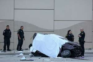 Houston Police officers investigate the scene of a fatal vehicle crash on the Gulf Freeway southbound feeder road near El Dorado Boulevard Wednesday, Feb. 28, 2018, in Friendswood, Texas. A woman and an infant died in the wreck.