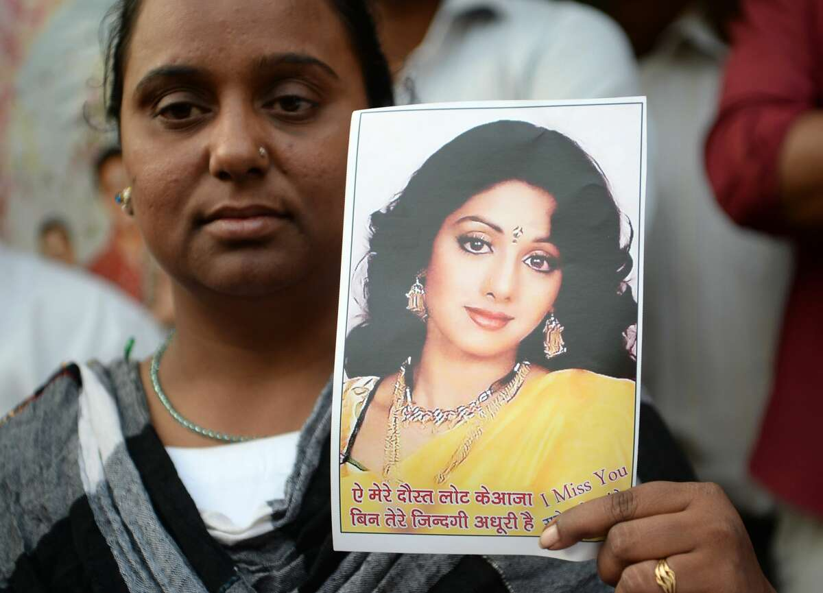 A woman holds a picture of late Bollywood actress Sridevi Kapoor as she stands outside her house before Sridevi's funeral in Mumbai on February 28, 2018. India has been mourning Bollywood superstar Sridevi Kapoor after her death in Dubai aged just 54, as police in the emirate said she drowned in her hotel bathtub. Sridevi -- one of the biggest names in Hindi cinema -- died late on February 24 after suffering a cardiac arrest in Dubai, where she had been attending her nephew's wedding.