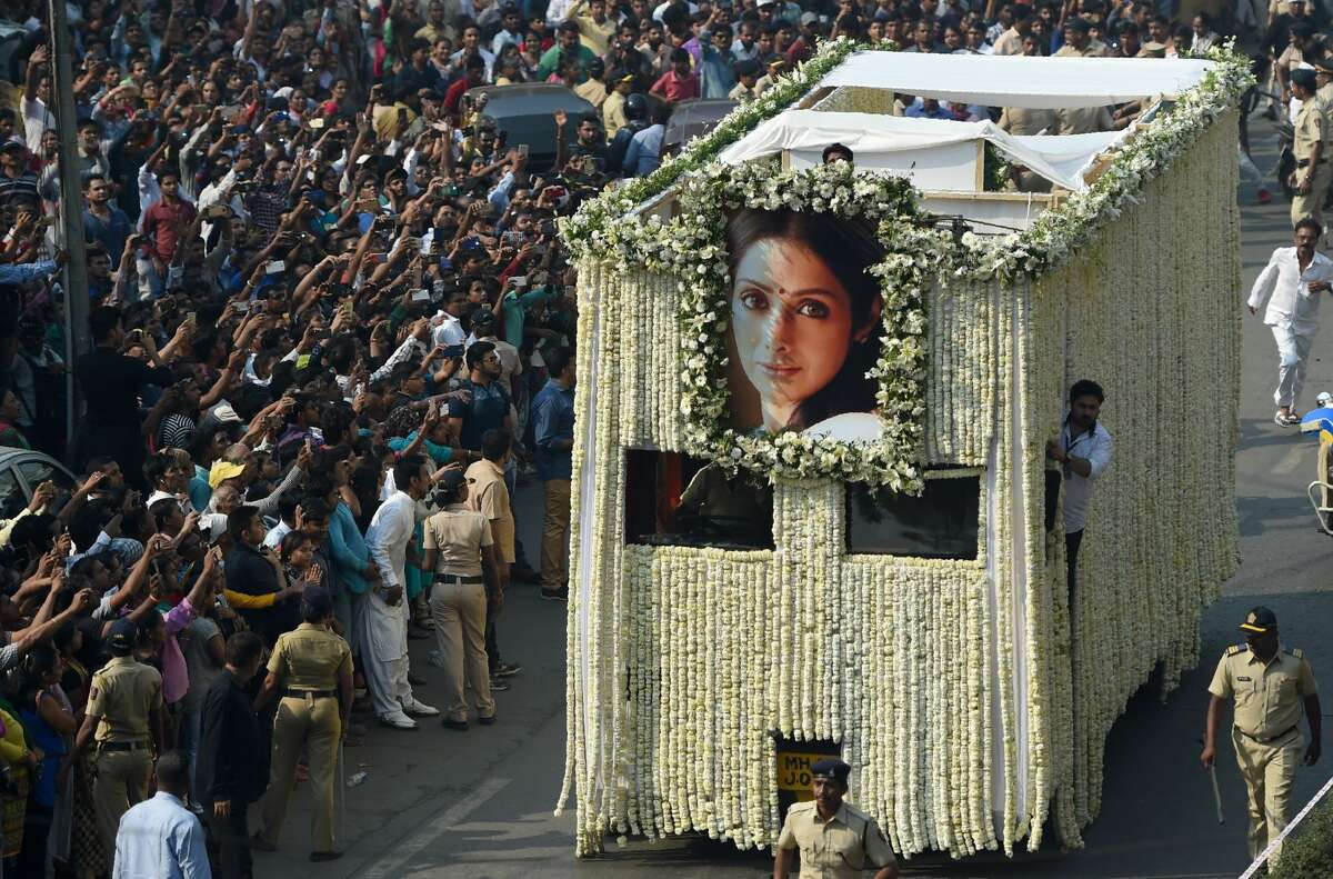 Indian fans watch as the funeral cortege of the late Bollywood actress Sridevi Kapoor passes through Mumbai ahead of her cremation on February 28, 2018. Thousands of heartbroken fans lined the streets of Mumbai February 28 as India said farewell to Bollywood legend Sridevi Kapoor following her shock death from accidental drowning in a Dubai hotel bathtub aged just 54.