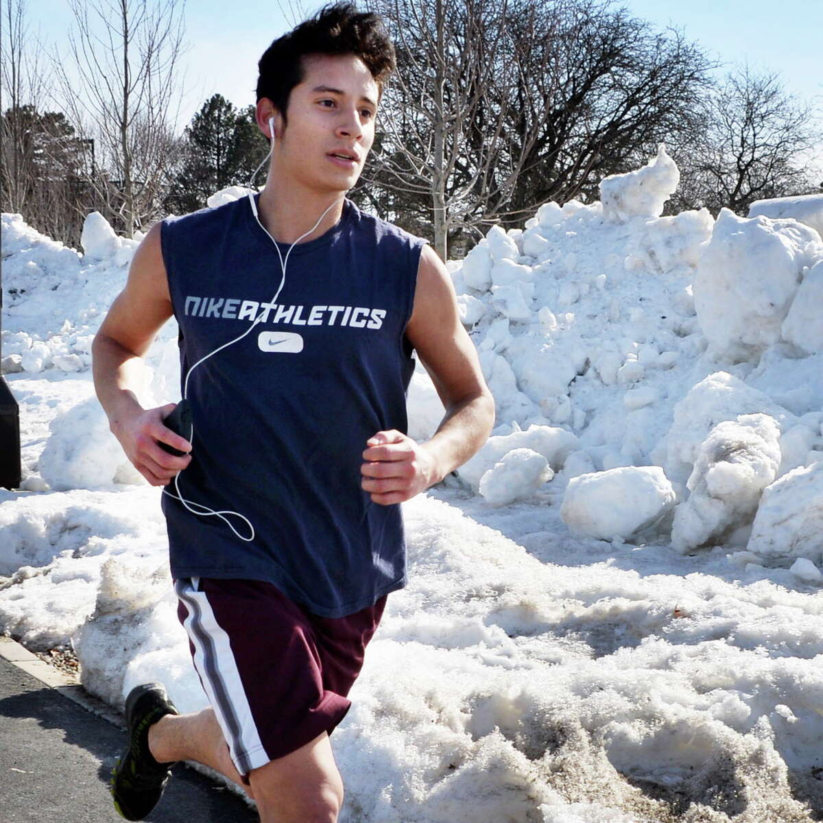 Dressed in shorts and t-shirt, UAlbany student Rogger Gutierrez of Kingston runs past snow banks on the main campus as temps finally begin to warm up Friday March 7, 2014, in Albany, NY. (John Carl D'Annibale / Times Union)