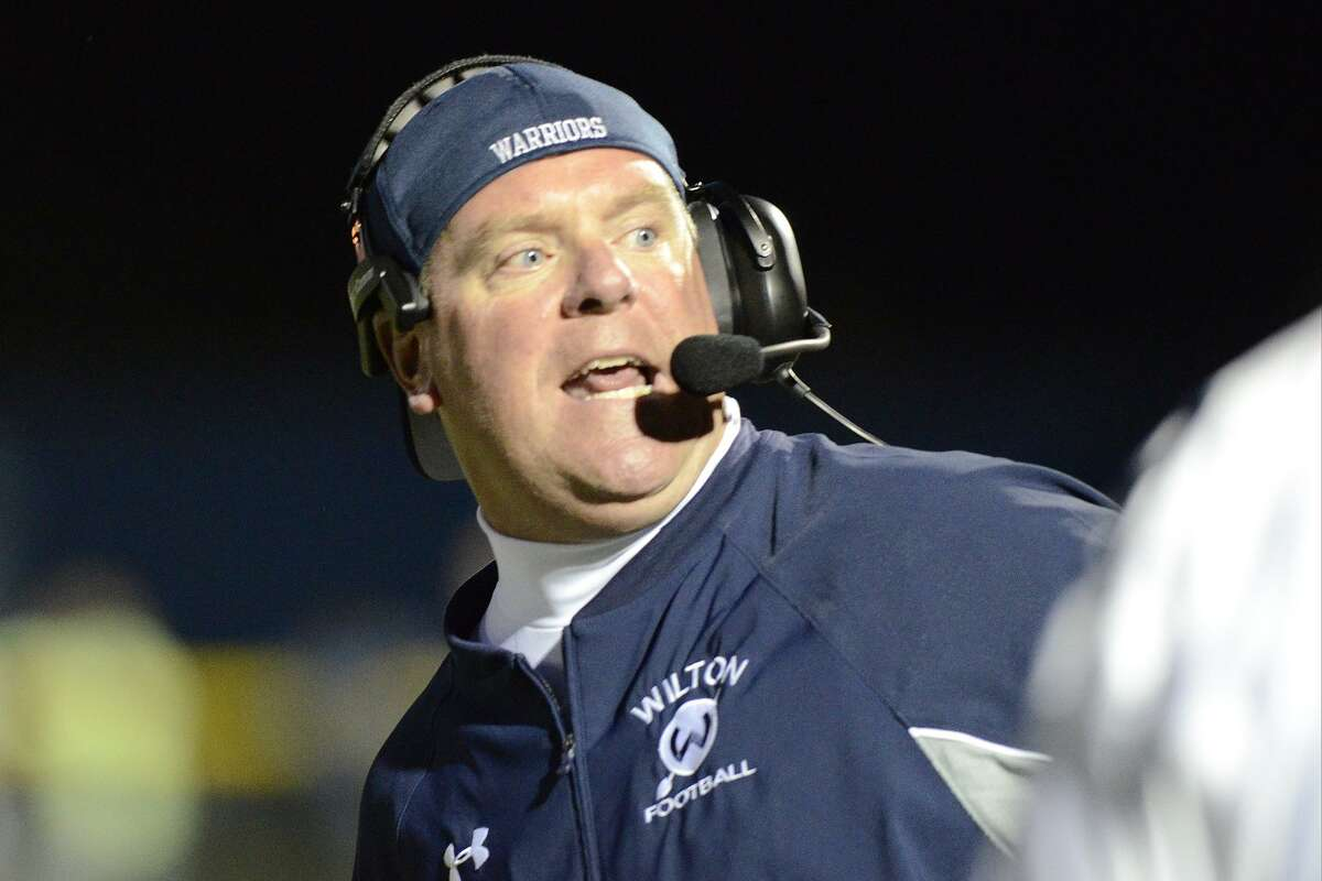 Wilton coach Bruce Cunningham directs his team as Staples High School hosts Wilton High School in varsity football in Westport, on Friday, Sept. 20, 2013. Cunningham stepped down from the position last month.