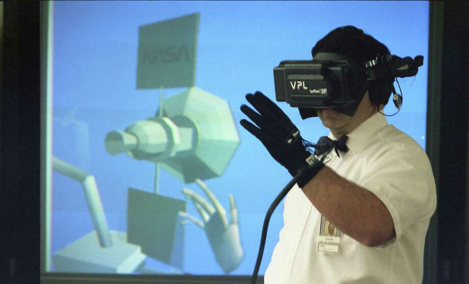 04/24/1992 - At Johnson Space Center, NASA scientist Bowen Loftin, working with virtual reality, gestures with a DataGlove, causing the hand on the screen - and on TV images in his headset - to respond in kind. Photo: Carlos Antonio Rios, Houston Chronicle / Houston Chronicle