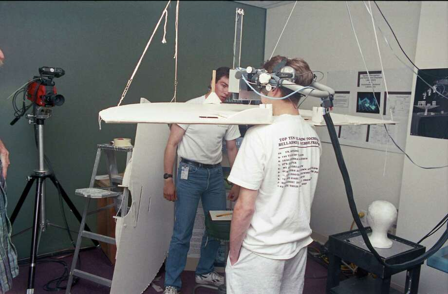 04/1992 - Jose Aguayo and Matt Malouf, in the headset, participate in a virtual reality experiment at NASA/Ames Research Center. Photo: Dwight Silverman, Houston Chronicle / Houston Chronicle