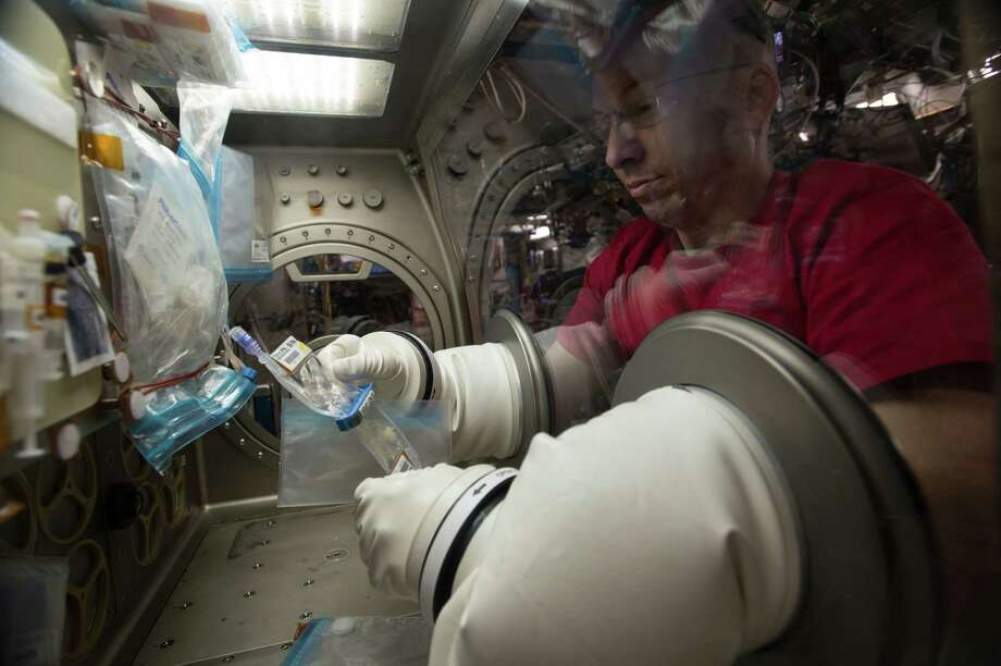 NASA astronaut Randy Bresnik works with the bioreactor bags containing lung tissue samples within the Microgravity Science Glovebox aboard the space station. The culture fluid will need to be frozen and returned to Earth for analysis. Photo: Credit: NASA