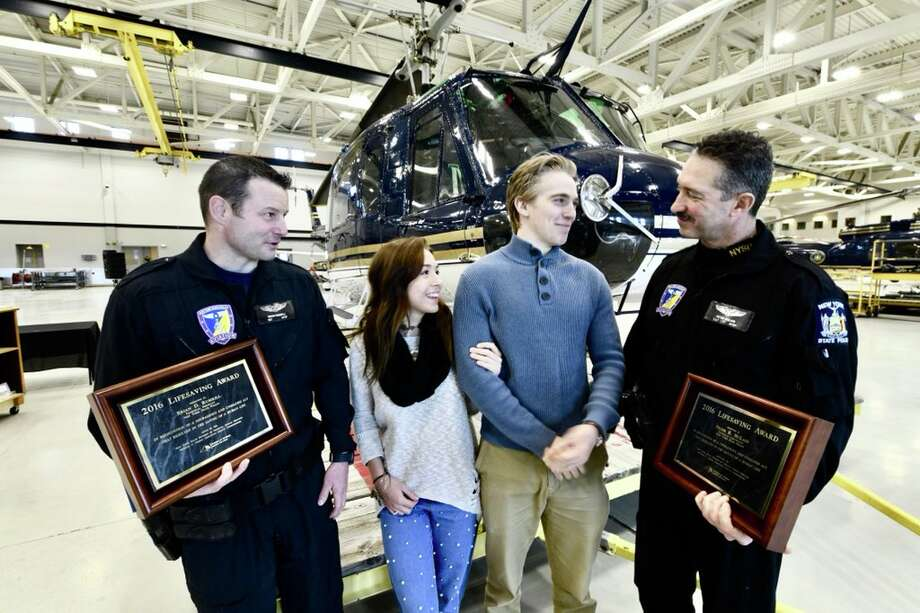 State Police pilots Technical Sgt. Brian D. Rumrill, far left, and Technical Lt. Peter R. McLain, far right, are honored on Feb. 28, 2018, with the Lifesaving Award for the Adirondack mountain rescue of Madison Popolizio and Blake Alois. (Skip Dickstein‏/Times Union) Photo: Skip Dickstein‏/Times Union