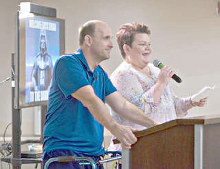 Amy Hanson, whose husband, Brian, left, continues to recover from a serious car crash last September, thanks the crowd at a trivia night event Friday to raise money for the family. Photo: For The Telegraph