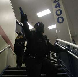 A police officer watches the staircase as his team assents the stairs at Atascocita High School during a mock school shooting drill on July 12, 2012. Law enforcement personnel from all over the Houston and surrounding areas took part in the exercises designed to simulate a hostage event in a school setting.