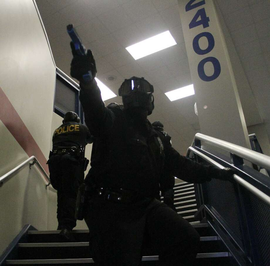 A police officer watches the staircase as his team ascends the stairs at Atasco cita High School near Houston during a mock school shooting drill in   2012. Photo: JASON FOCHTMAN, The Observer