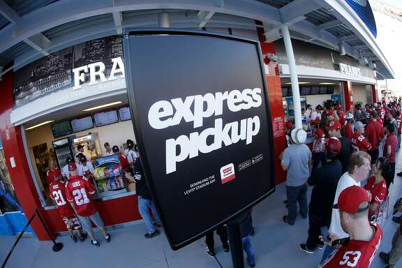 In this Sept. 14, 2014 photo, fans wait in an express pickup line at a Levi's Stadium concessions stand during an NFL football game between the San Francisco 49ers and the Chicago Bears in Santa Clara, Calif. If 49ers CEO Jed York realizes his vision, Levi�s Stadium will channel Silicon Valley�s ingenuity to become known as a technology temple programmed to pamper and connect fans who are more accustomed to being corralled in congested venues with little or no Internet access. (AP Photo/Noah Berger)