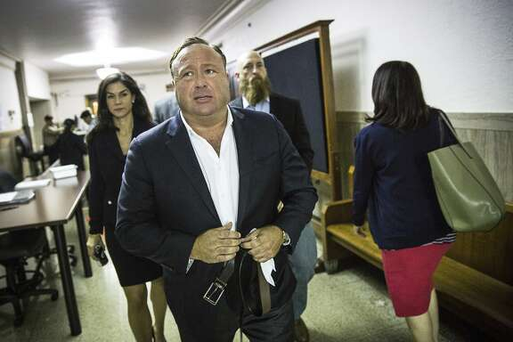"In this April 17, 2017, file photo, ""Infowars"" host Alex Jones arrives at the Travis County Courthouse in Austin, Texas. Infowars, a website that suggested survivors of the Florida school shooting were coached on their pleas for gun control, says its video account was temporarily frozen by YouTube. (Tamir Kalifa/Austin American-Statesman via AP, File)"