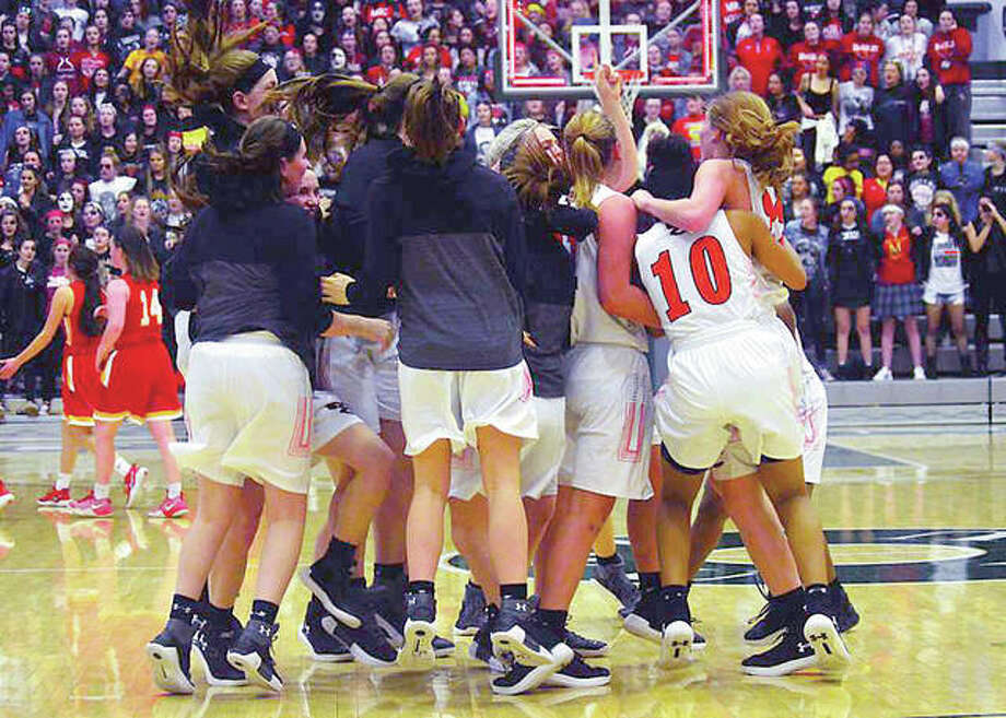 Members of the Edwardsville girls basketball team celebrate their super-sectional victory over Chicago Mother McCauley Monday night in Bloomington Photo: Matt Kamp | For The Telegraph