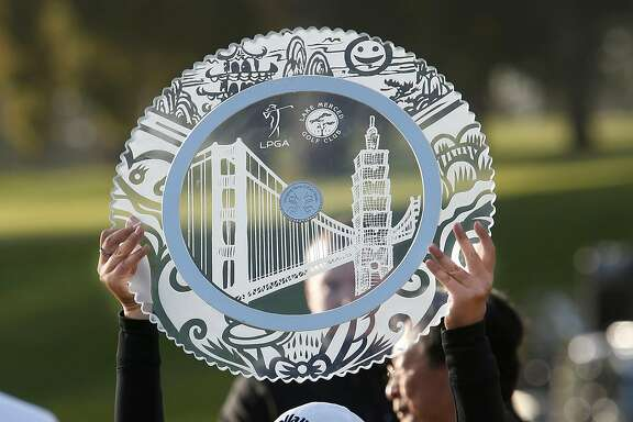 Lydia Ko raises the champions trophy after winning the Swinging Skirts LPGA classic at Lake Merced Golf Club in Daly City, Calif., on Sunday April 27, 2014, with a score of 12 under par.