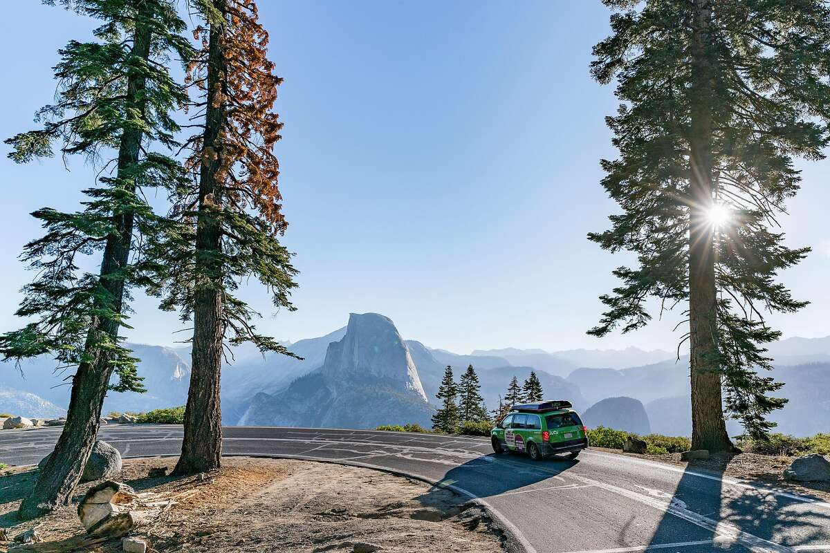 A Jucy van passes by Half Dome in Yosemite National Park.