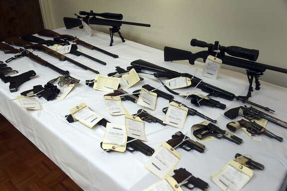 A cache of seized weapons is displayed during a press conference in Los Angeles, Calif., Tuesday, Feb. 6, 2018. Authorities have seized more than two dozen guns and thousands of rounds of ammunition from a California man, nearly five months after a judge signed an order prohibiting him from possessing firearms. (AP Photo/Mike Balsamo)