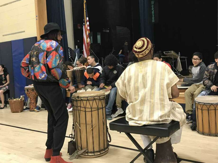 Students at Hill Central School play drums with Michael Mills and Cecelia Calloway during the school's Black History Month celebration. Photo: Brian Zahn / Hearst Connecticut Media