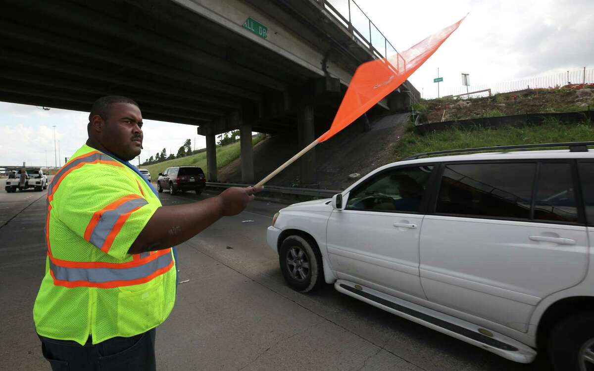 Andre McDaniel directs traffic as Houston Police respond to a minor accident on May 30.