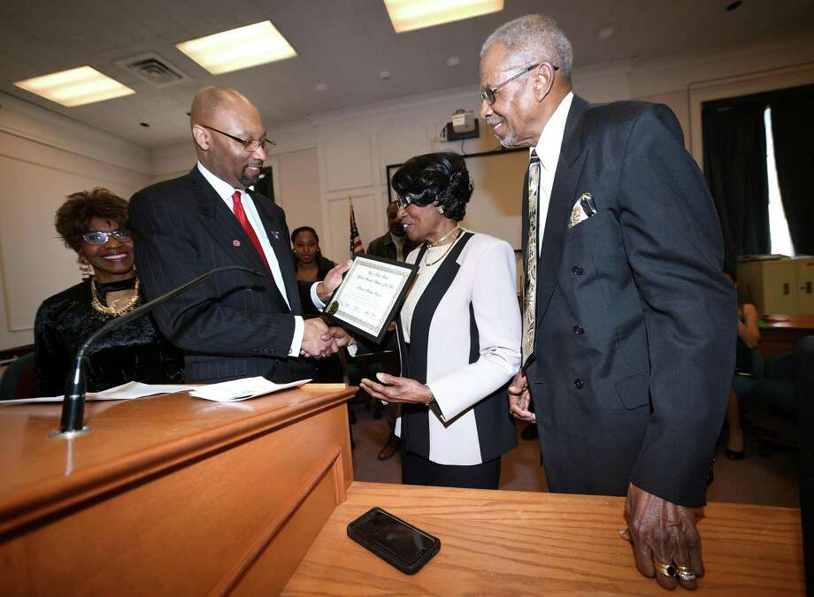From left, Bea Johnson, president of the West Haven Black Heritage Committee, watches master of ceremonies Steven R. Mullins present Roberta and Moses Douglas the West Haven African-American Citizens of the Year Award  at West Haven City Hall Wednesday. Photo: Arnold Gold / Hearst Connecticut Media / New Haven Register