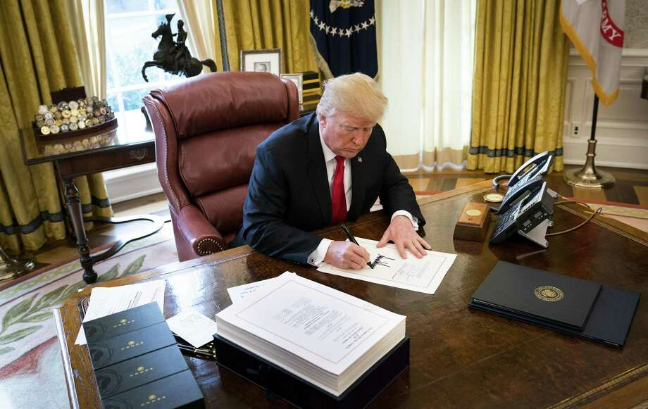 President Donald Trump signs the tax reform bill in the Oval Office of the White House in Washington, Dec. 22. Support for the law though not for Trump himself is growing even among Democrats, buoying Republican hopes for this years congressional elections. Photo: DOUG MILLS /NYT / NYTNS