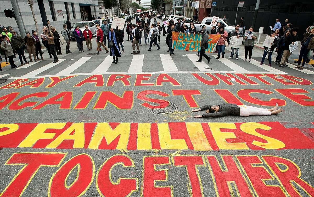 Carolina Collazos lies in an intersection as protesters rally against immigration raids outside the Department of Homeland Security offices on Sansome St. on Wednesday, Feb. 28, 2018, in San Francisco.