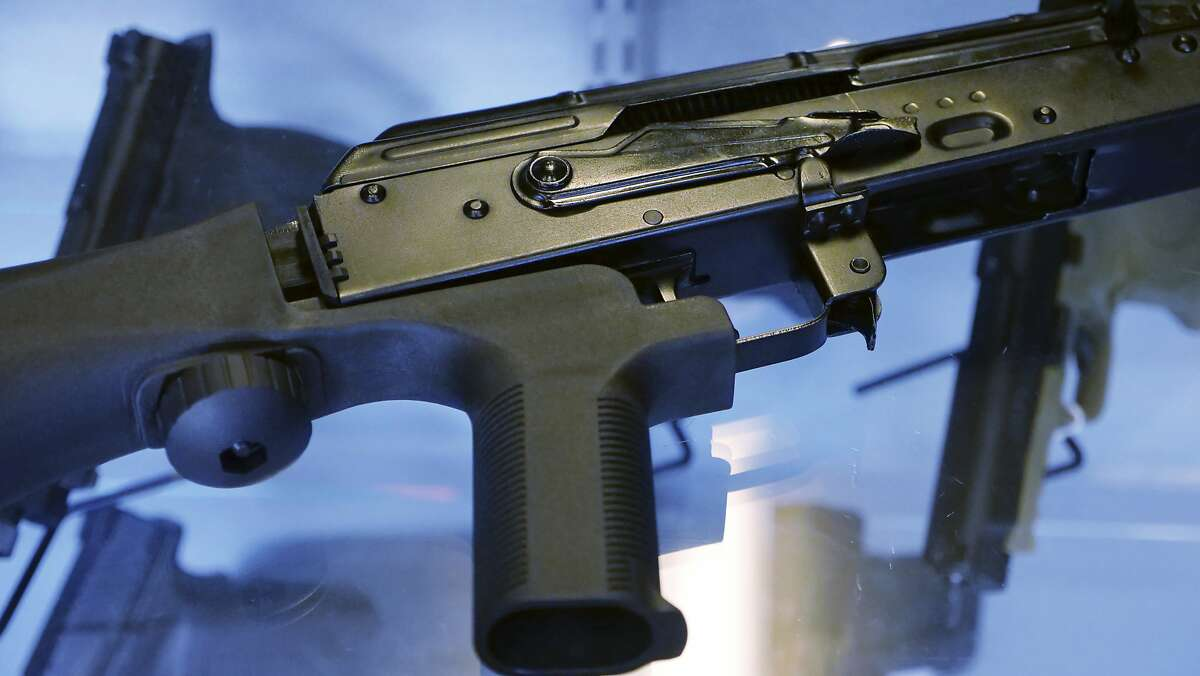 """FILE - In this Oct. 4, 2017, file photo, a device called a """"bump stock"""" is attached to a semi-automatic rifle at the Gun Vault store and shooting range in South Jordan, Utah. Some states and cities are taking the lead on banning bump stocks as efforts stall in Washington. The controversial device was used in the Las Vegas shooting, allowing a semi-automatic rifle to mimic a fully automatic firearm. Gun-control advocates say the push fits a pattern in gun politics: inaction in Washington that forces states to take charge. (AP Photo/Rick Bowmer, File)"""