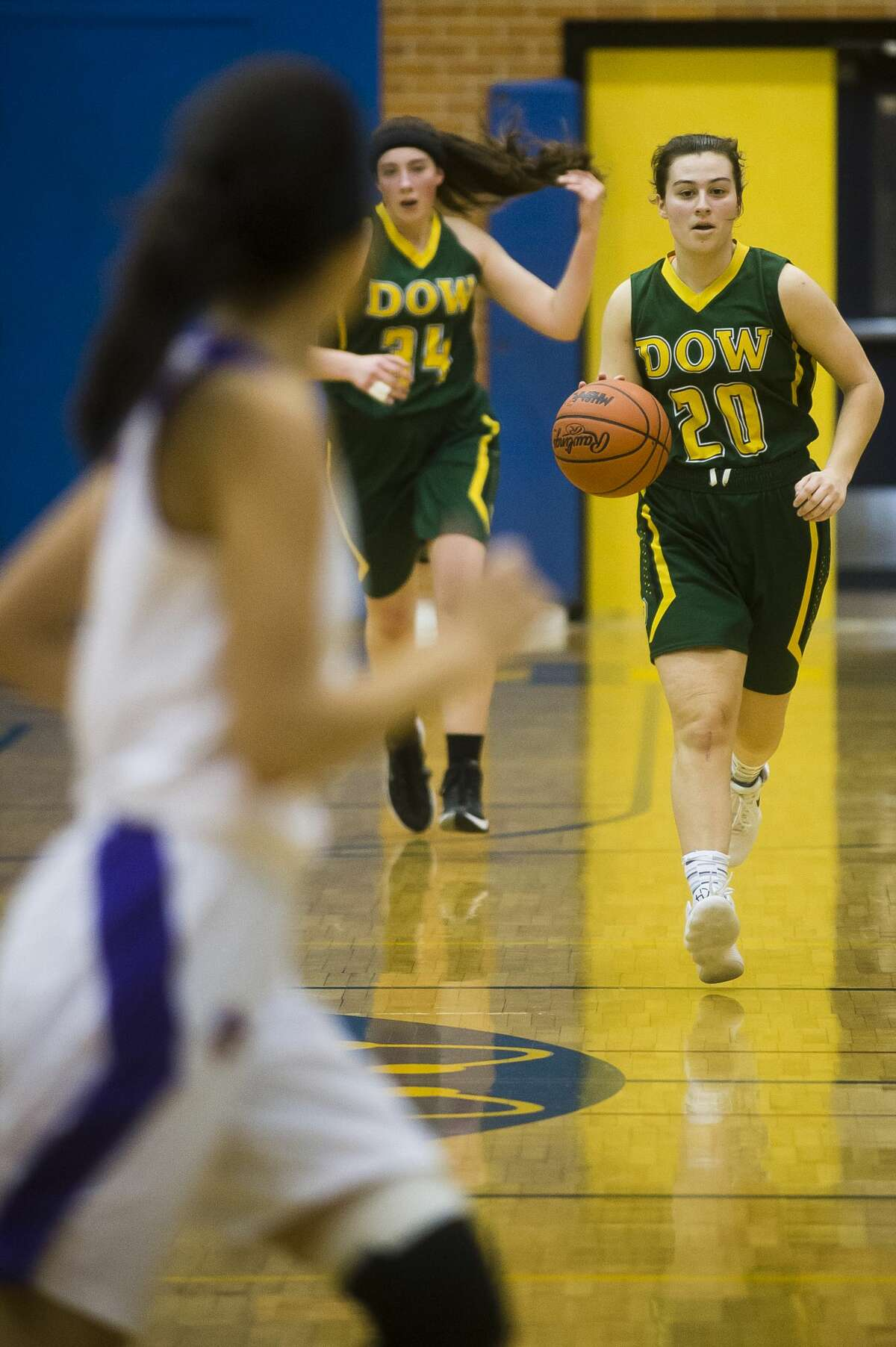 Dow junior Maizie Taylor dribbles down the court while sophomore Alyssa Keptner follows behind her during the Chargers' district semifinals game against Bay City Central on Wednesday, Feb. 28, 2018 at Midland High School. (Katy Kildee/kkildee@mdn.net)
