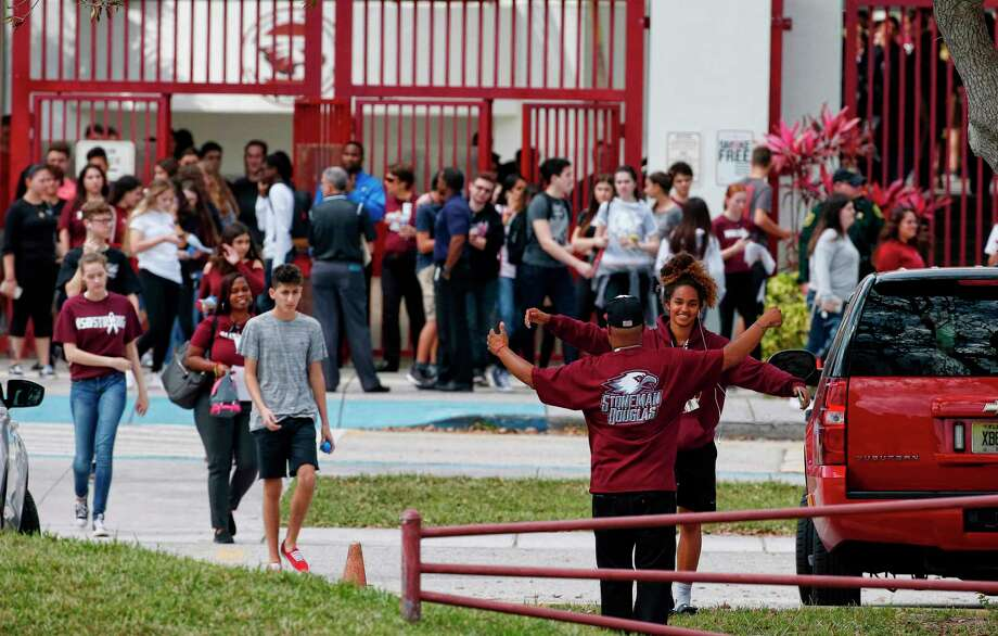 Marjory Stoneman Douglas High School students, staff and teachers exit the building following their return to school in Parkland, Florida on February 28, 2018. A former student, Nikolas Cruz, opened fire at Marjory Stoneman Douglas High School leaving 17 people dead and 15 injured on February 14. Students grieving for slain classmates prepared for an emotional return Wednesday to their Florida high school, where a mass shooting shocked the nation and led teen survivors to spur a growing movement to tighten America's gun laws. The community of Parkland, Florida, where residents were plunged into tragedy two weeks ago, steeled itself for the resumption of classes at Marjory Stoneman Douglas High School, where nearby flower-draped memorials and 17 white crosses pay tribute to the 14 students and three staff members who were murdered by a former student.  / AFP PHOTO / RHONA WISERHONA WISE/AFP/Getty Images Photo: RHONA WISE / AFP or licensors