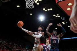 Stanford's Daejon Davis scores over Arizona's DeAndre Ayton (#13) during a Pac-12 basketball game at Maples Pavilion on January 20, 2018 in Stanford, CA.
