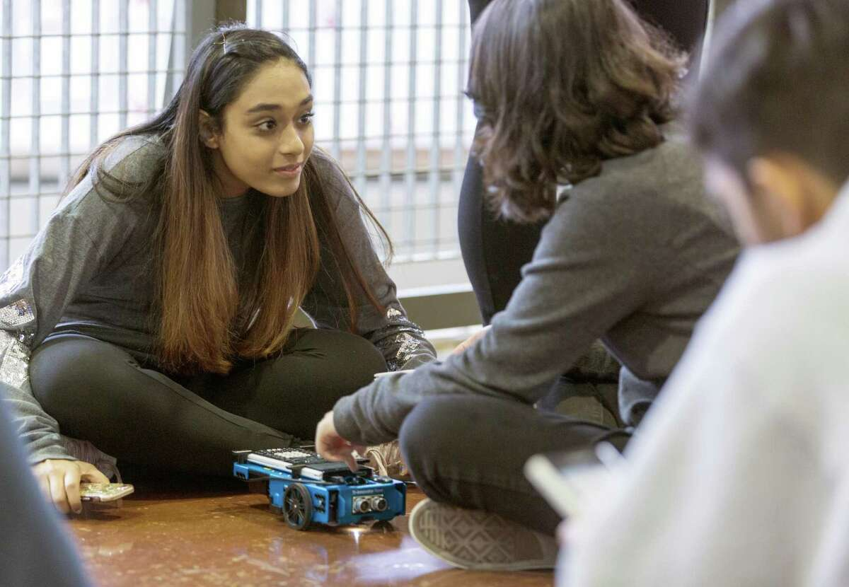 Reagan High School sophomore Bayaan Musa talks with freshman Aurea Le as the two work to program a Texas Instruments rover during a STEM day event.