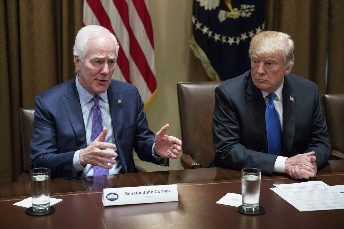 Senate Majority Whip John Cornyn, a Republican from Texas, left, speaks as U.S. President Donald Trump listens during a meeting with bipartisan members of Congress to discuss school and community safety in the Cabinet Room of the White House in Washington, D.C., U.S. on Wednesday, Feb. 28, 2018. Trump has vowed to pass new laws designed to curb campus gun violence following the Feb. 14 shooting at a Parkland, Florida high school in which 17 people were killed and more than a dozen more wounded. Photographer: Joshua Roberts/Bloomberg