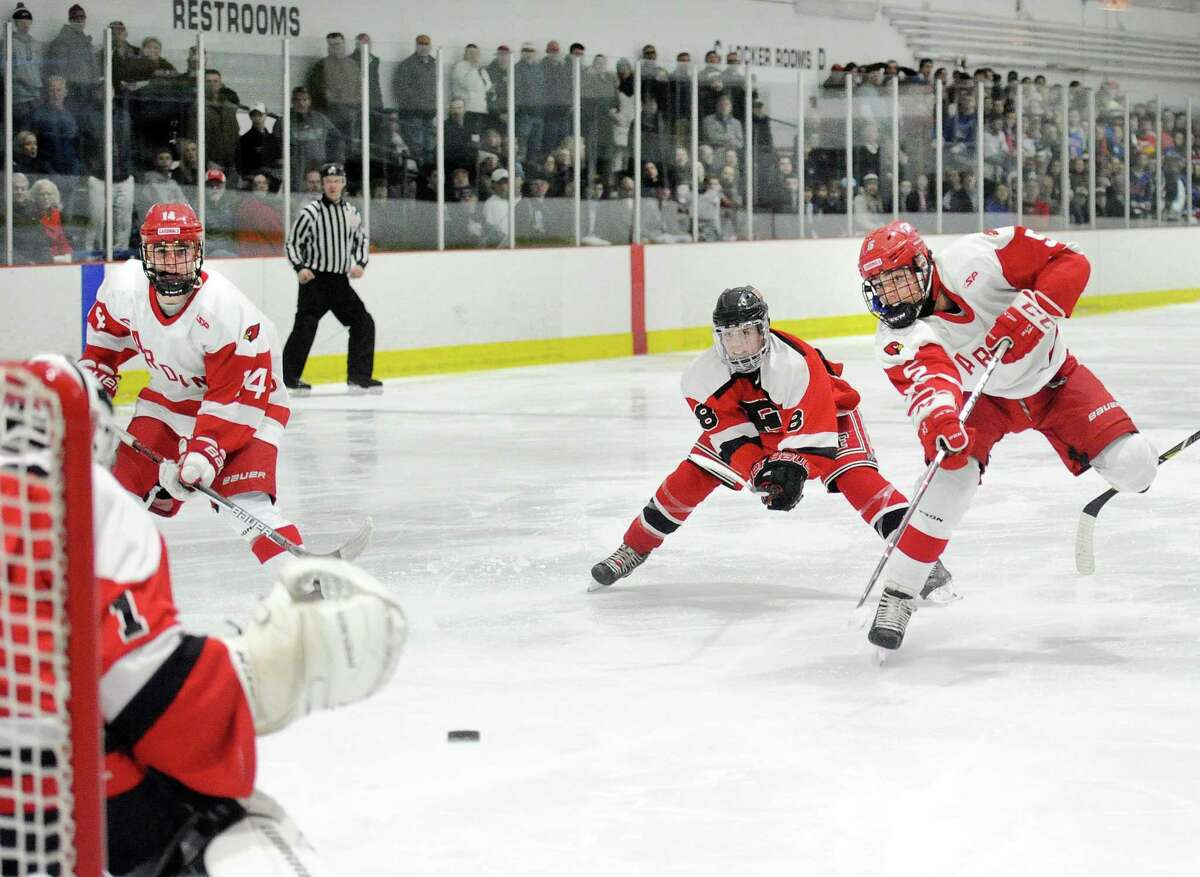 At right, Nicolas Pelletier-Martinelli (#5) of Greenwich beats Faifield defender Kyle Mazza (#8), getting off a second period slapshot that beat Fairfield goalie Dawson Gunn, left, for a goal during the FCIAC boys ice hockey semi-final game between Greenwich High School and Fairfield Combined High Schools at the Darien Ice Rink, Conn., Wednesday, Feb. 28, 2018.