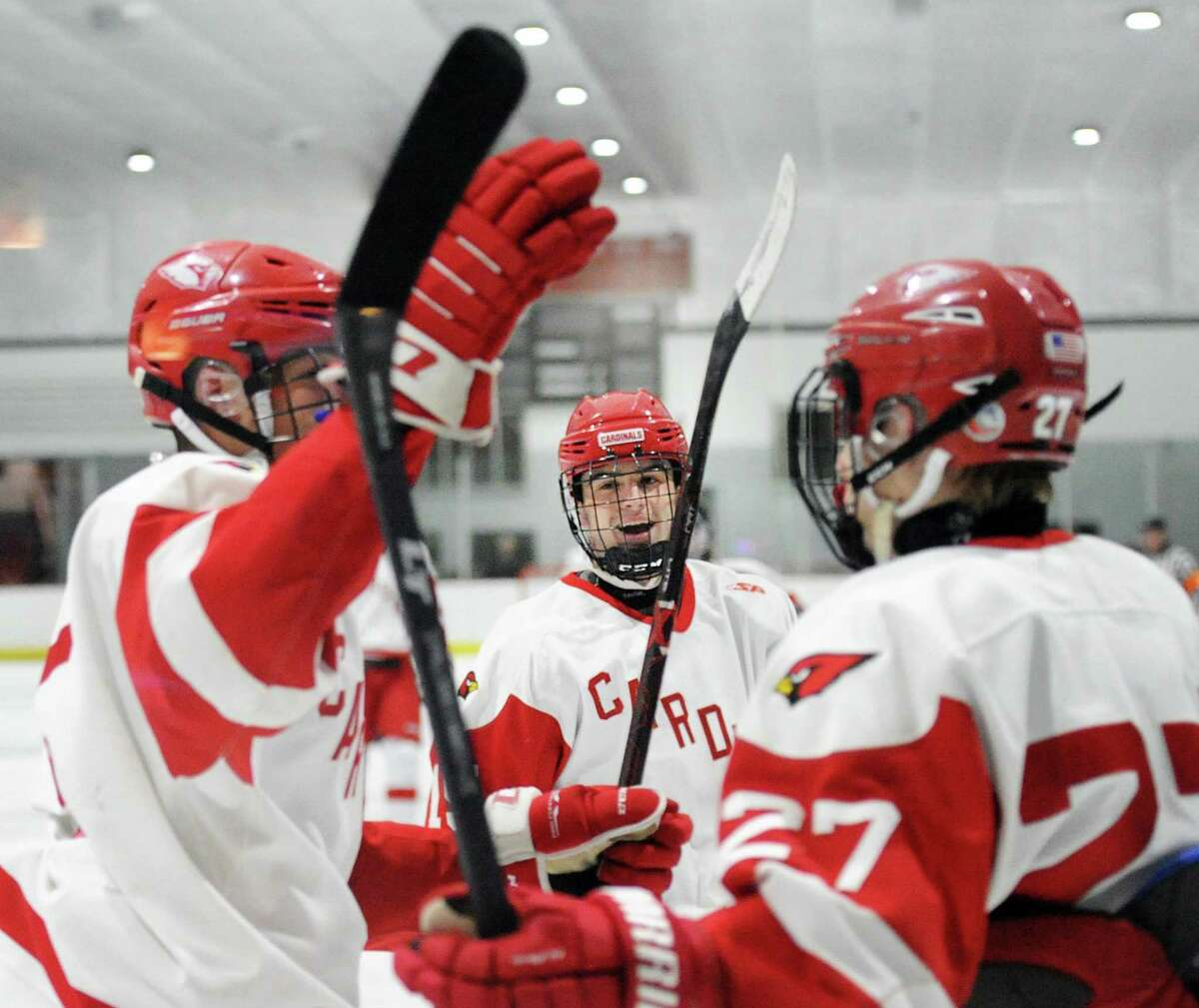 At center, Greenwich's Matthew Davey smiles after teammate Nicolas Pelletier-Martinelli, left, scored a second period goal. Joining the celebration at right is Nikita Kovalev on Wednesday in Greenwich.