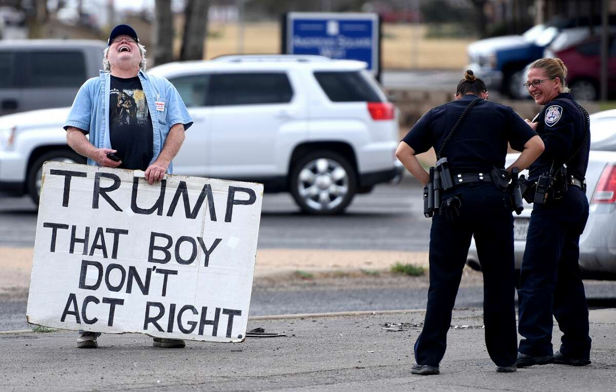 """Gale McCray shares a laugh with Midland Police Department officers while protesting with a sign Feb. 28, 2018, at the corner of Andrews Highway and Midland Drive. McCray is a retiree who lives in Ft. Worth, Texas, and has become a small internet sensation for making appearances across the country holding a sign that states """"TRUMP THAT BOY DONT ACT RIGHT."""" McCray passed through Midland with his sign Feb. 28, 2018, and spent about 2 hours standing at the corner of Andrews Highway and Midland Drive. James Durbin/Reporter-Telegram"""