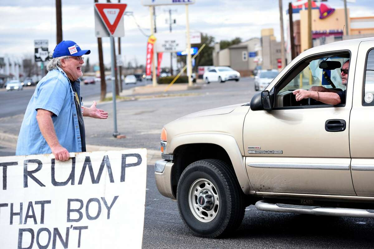 """A motorist yells at Gale McCray as he stands holding a sign that states """"TRUMP THAT BOY DONT ACT RIGHT,"""" Feb. 28, 2018, at the corner of Andrews Highway and Midland Drive. McCray is a retiree who lives in Ft. Worth, Texas, and has become a small internet sensation for making appearances across the country holding the sign. McCray passed through Midland Feb. 28, 2018, and spent about 2 hours standing at the corner of Andrews Highway and Midland Drive. James Durbin/Reporter-Telegram"""