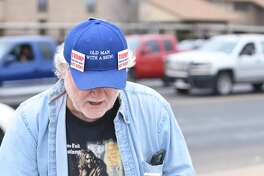"""Gale McCray, a retiree who lives in Ft. Worth, Texas, has become a small internet sensation for making appearances across the country holding a sign that states """"TRUMP THAT BOY DONT ACT RIGHT."""" McCray passed through Midland with his sign Feb. 28, 2018. Pictured, McCray carries a notebook while protesting and records the feedback he recieves from motorists and passersby.  McCray spent about 2 hours standing at the corner of Andrews Highway and Midland Drive.  James Durbin/Reporter-Telegram"""