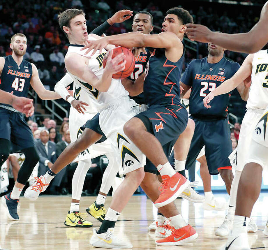 Iowa forward Nicholas Baer (51) strips the ball from Illinois guard Mark Smith (13) during the first half of Wednesday's first-round game of the Big Ten men's tournament in New York. Illinois forward Michael Finke (43) and guard Aaron Jordan (23) watch. Photo: AP