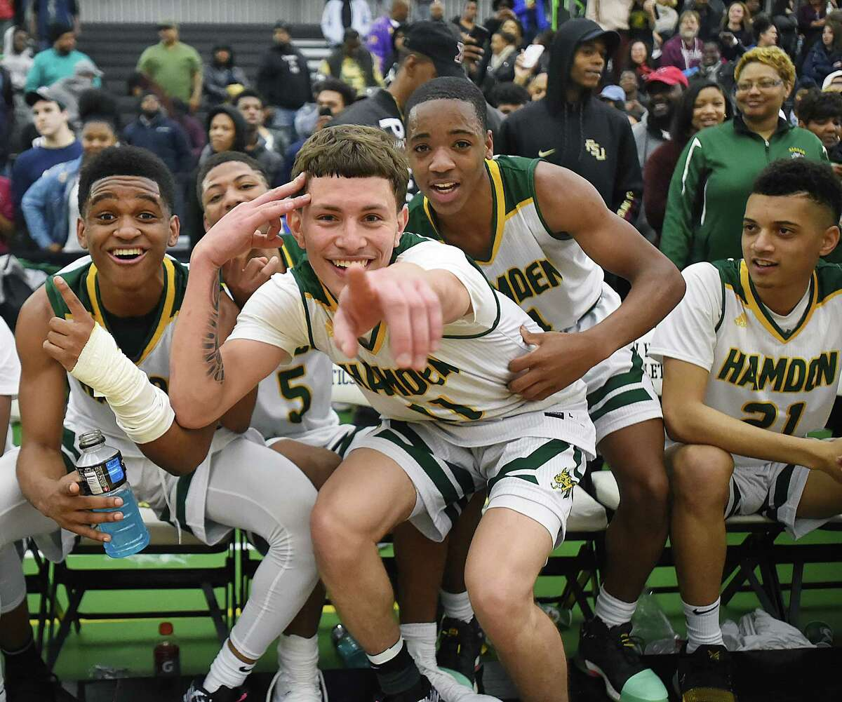 Hamden's Victor Rosario (11) the tournament MVP and his teammates celebrate their SCC championship win, defeating Hillhouse 67-49, Wednesday, Feb. 28, 2018, at the Floyd Little Athletic Center in New Haven.