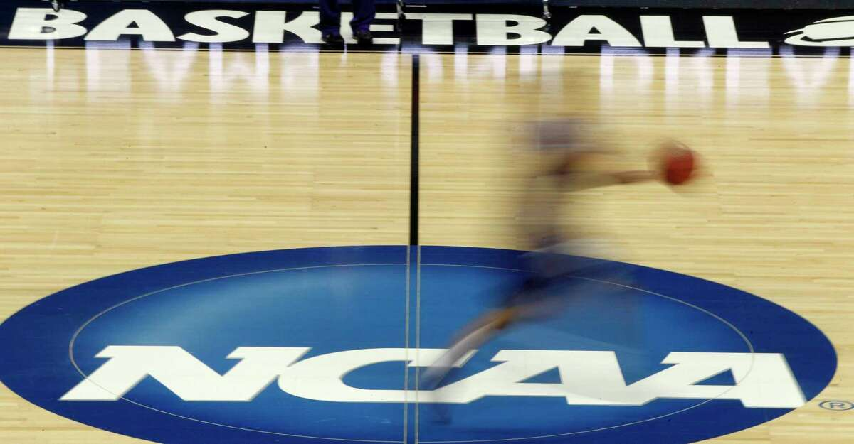 FILE - In this March 14, 2012, file photo, a player runs across the NCAA logo during practice in Pittsburgh before an NCAA tournament college basketball game. (AP Photo/Keith Srakocic, File)