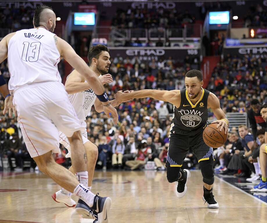 Golden State Warriors guard Stephen Curry (30) drives to the basket against Washington Wizards forward Tomas Satoransky, center, and center Marcin Gortat (13), of Poland, during the first half of an NBA basketball game Wednesday, Feb. 28, 2018, in Washington. Photo: Nick Wass, Associated Press