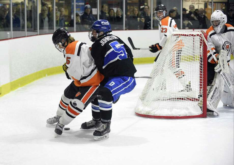 Ridgefield Herny Garlick and Darien William Johnston battle for the puck as Ridgefield goalie Sean Gordon looks on during a FCIAC Boys Ice Hockey Semi-Final game at the Darien Ice House on Wednesday, Feb. 28, 2018 in Darien, Connecticut. Photo: Matthew Brown / Hearst Connecticut Media / Stamford Advocate