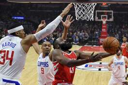 Houston Rockets guard James Harden, right, shoots as Los Angeles Clippers forward Tobias Harris, left, and guard C.J. Williams defend during the first half of an NBA basketball game Wednesday, Feb. 28, 2018, in Los Angeles. (AP Photo/Mark J. Terrill)